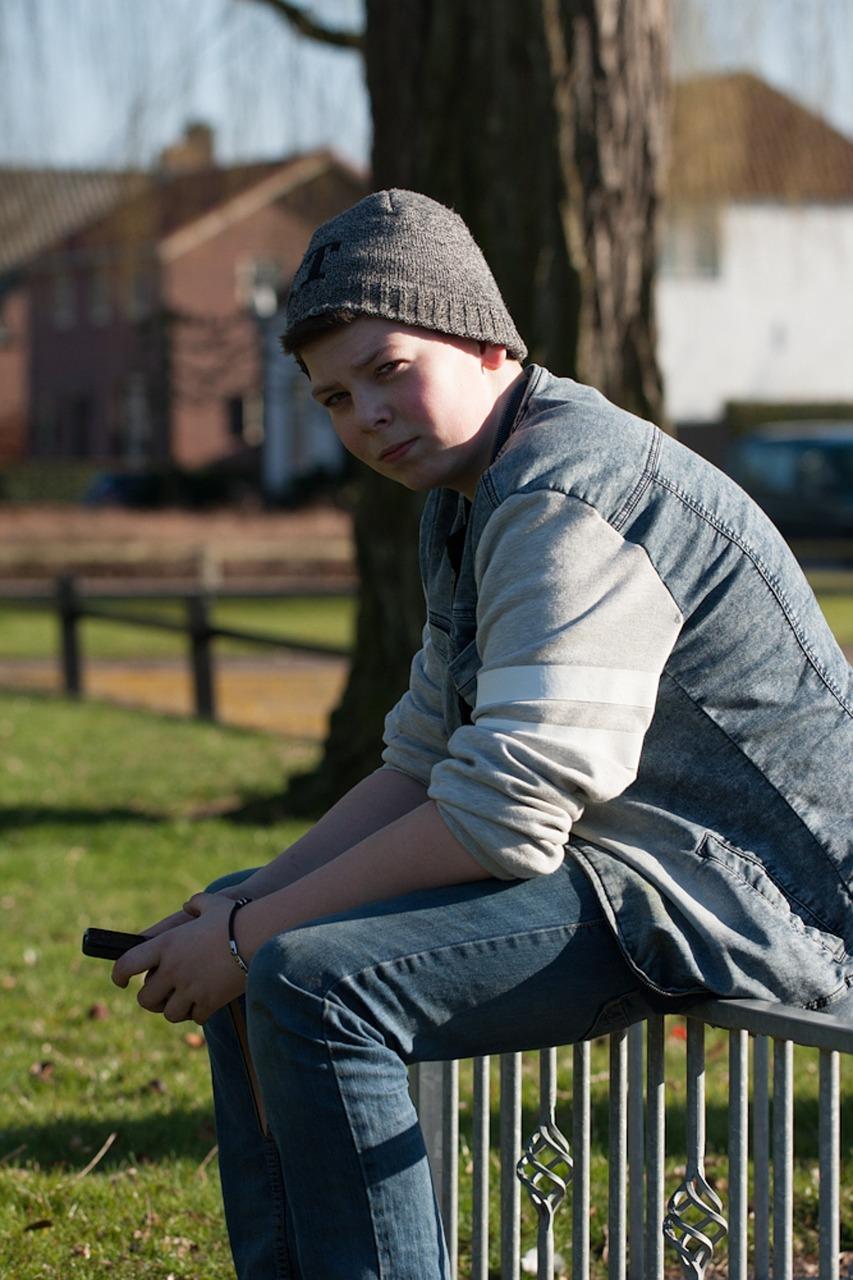 trudny nastolatek siedzący na płocie